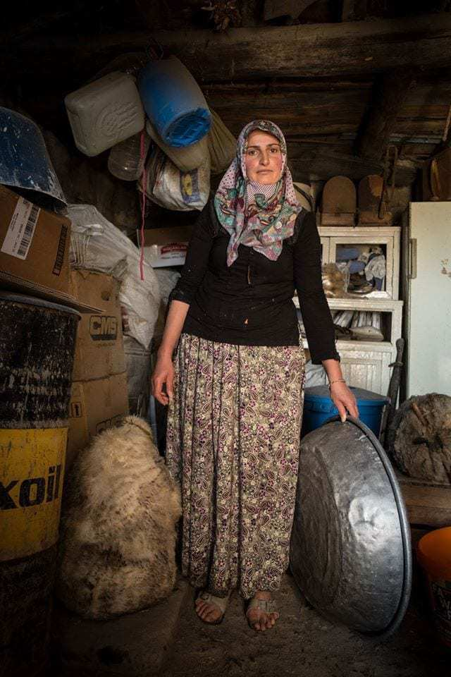 A local woman spends her morning making cheese in a sheepskin.