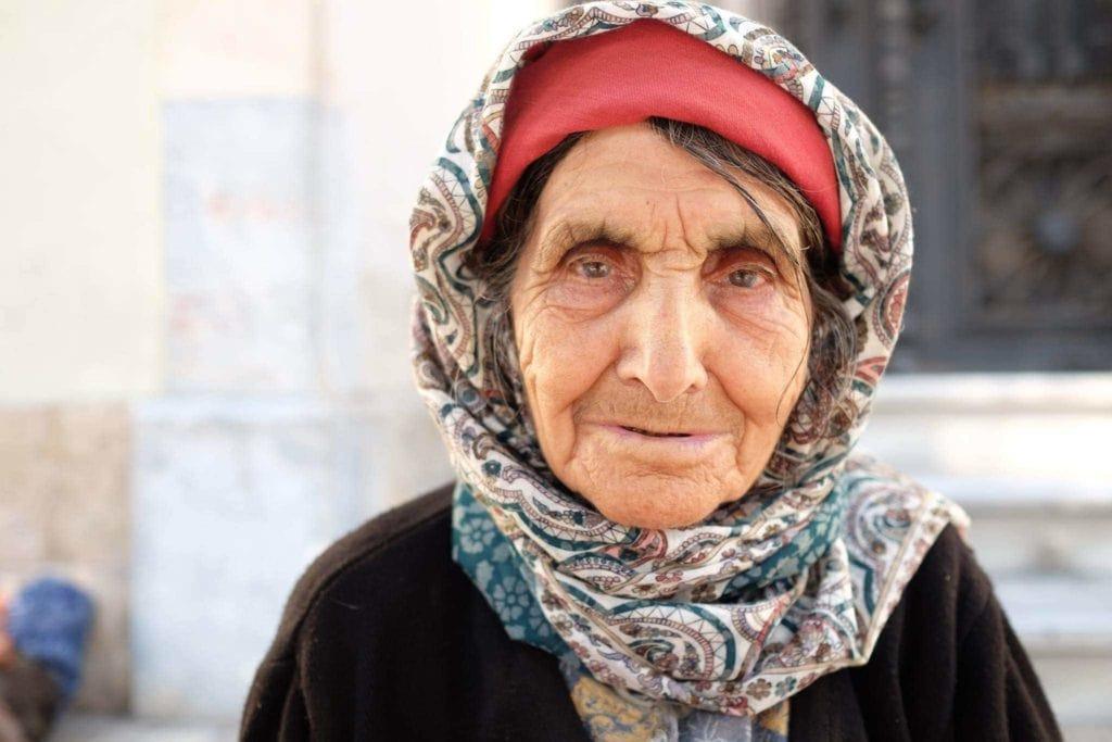 An elderly woman selling flowers in Antalya.