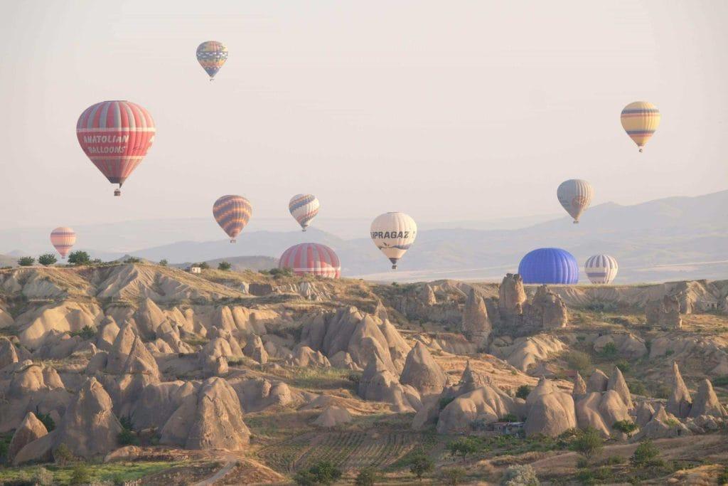 Hot air balloons flying high over Goreme, Cappadocia. Photo: Genevieve Hathaway Photography.