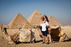 Shutterstock: Couple with camels in front of giza pyramids